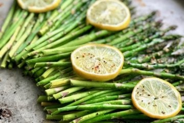 lemon butter asparagus garnished with lemon slices on a sheet pan