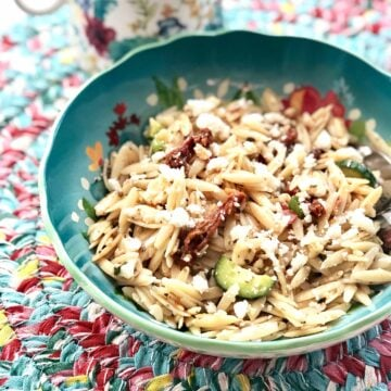 blue bowl of orzo pasta with tomatoes, cucumbers and onions on a colorful placemat