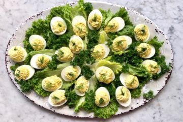 an entire platter of deviled eggs on lettuce leaves