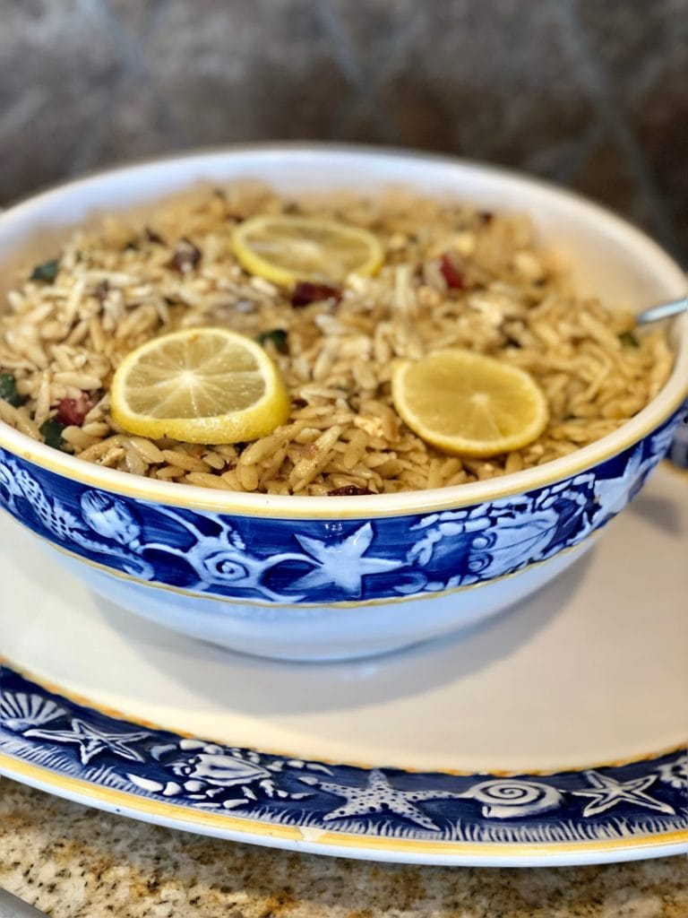 sun-dried tomato orzo pasta in a white dish with blue band