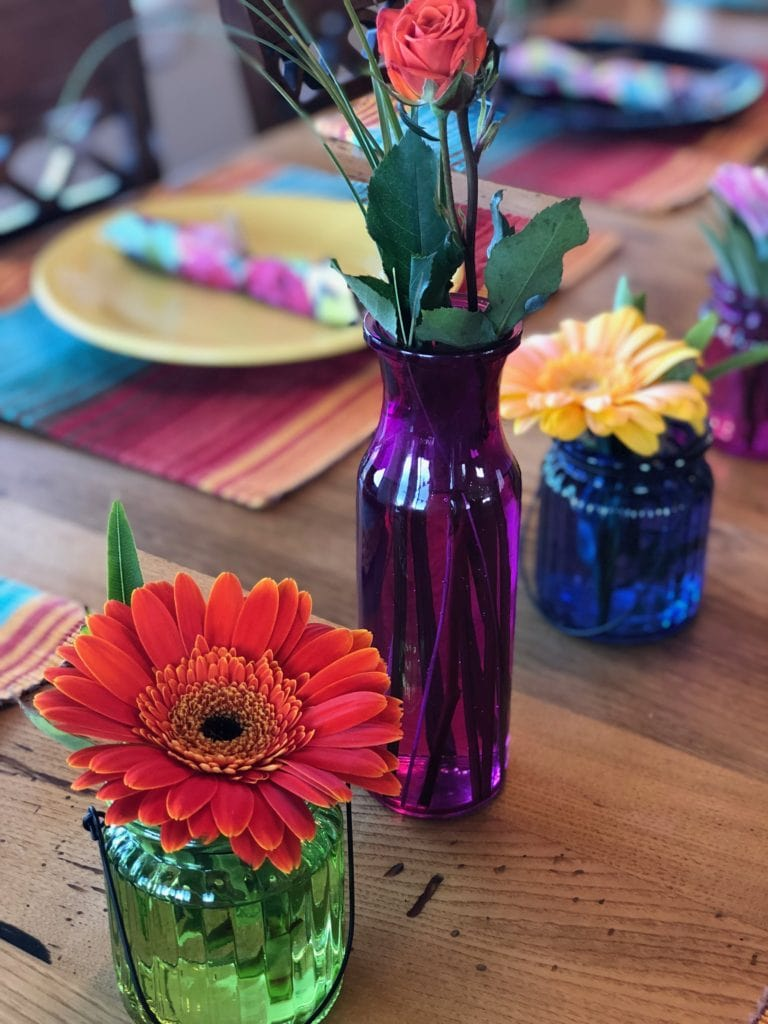 bright gerber daisies in colored vases on a wooden table