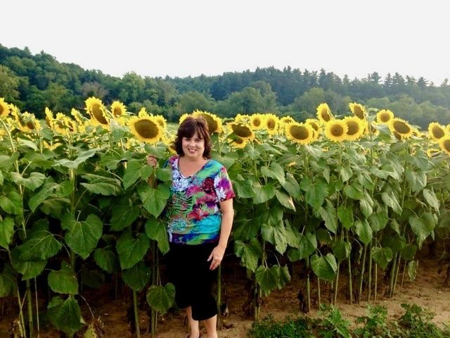 Debi, the author of Quiche My Grits, in a field of sunflowers