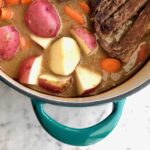 potatoes, carrots and roast beef in a savory gravy in a blue dutch oven