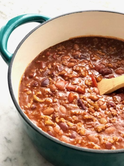 a big dutch oven full of campfire chili with beans, tomatoes and a wooden spoon stirring it together
