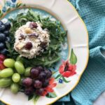 scoop of chicken salad on floral plate with fruit
