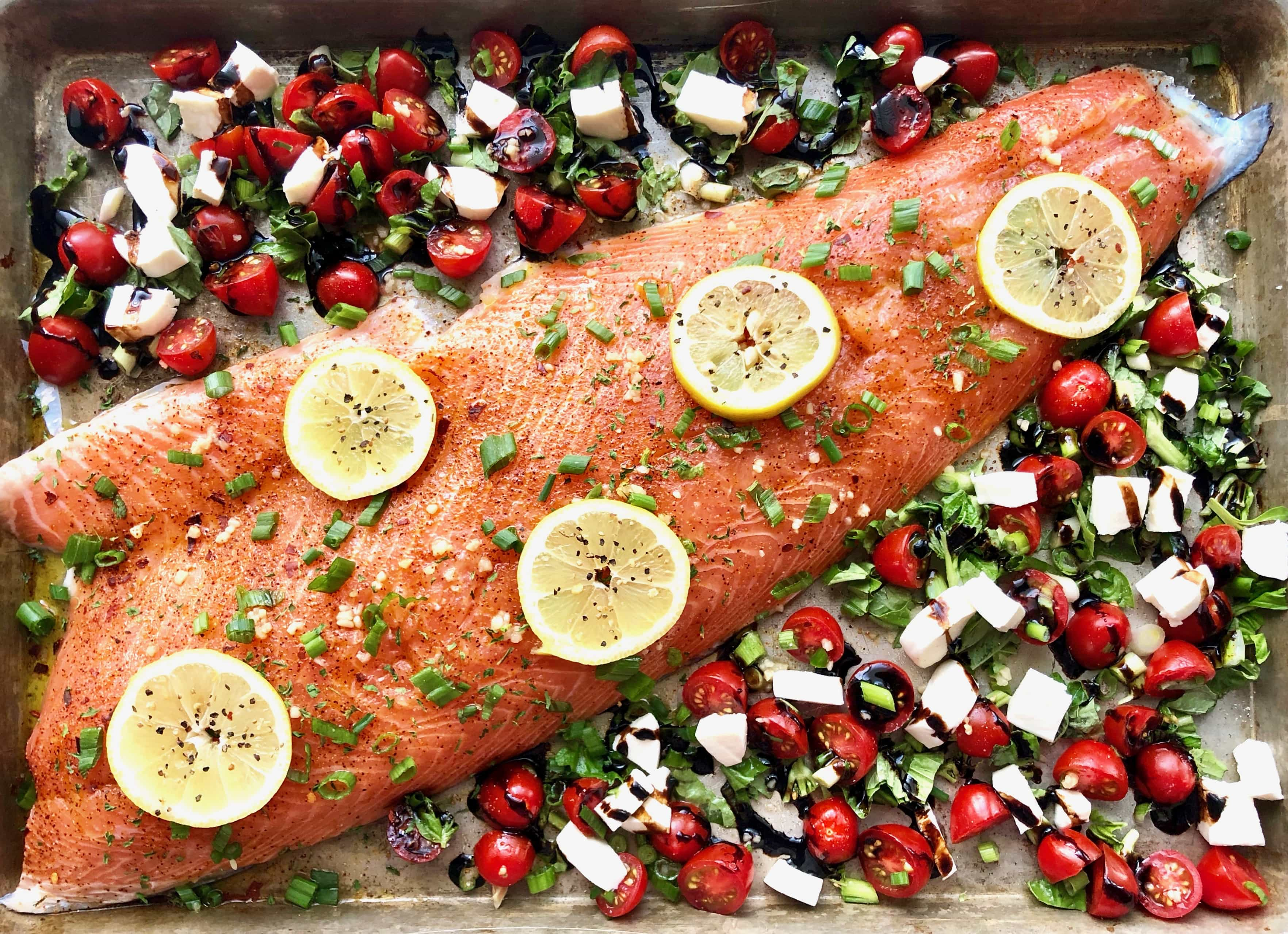 whole salmon on a sheet pan covered with lemon slices