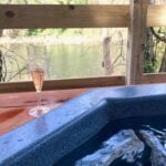 hot tub by river with champagne in background