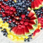 blueberries, raspberries, grapes, pineapple and strawberries on a white platter