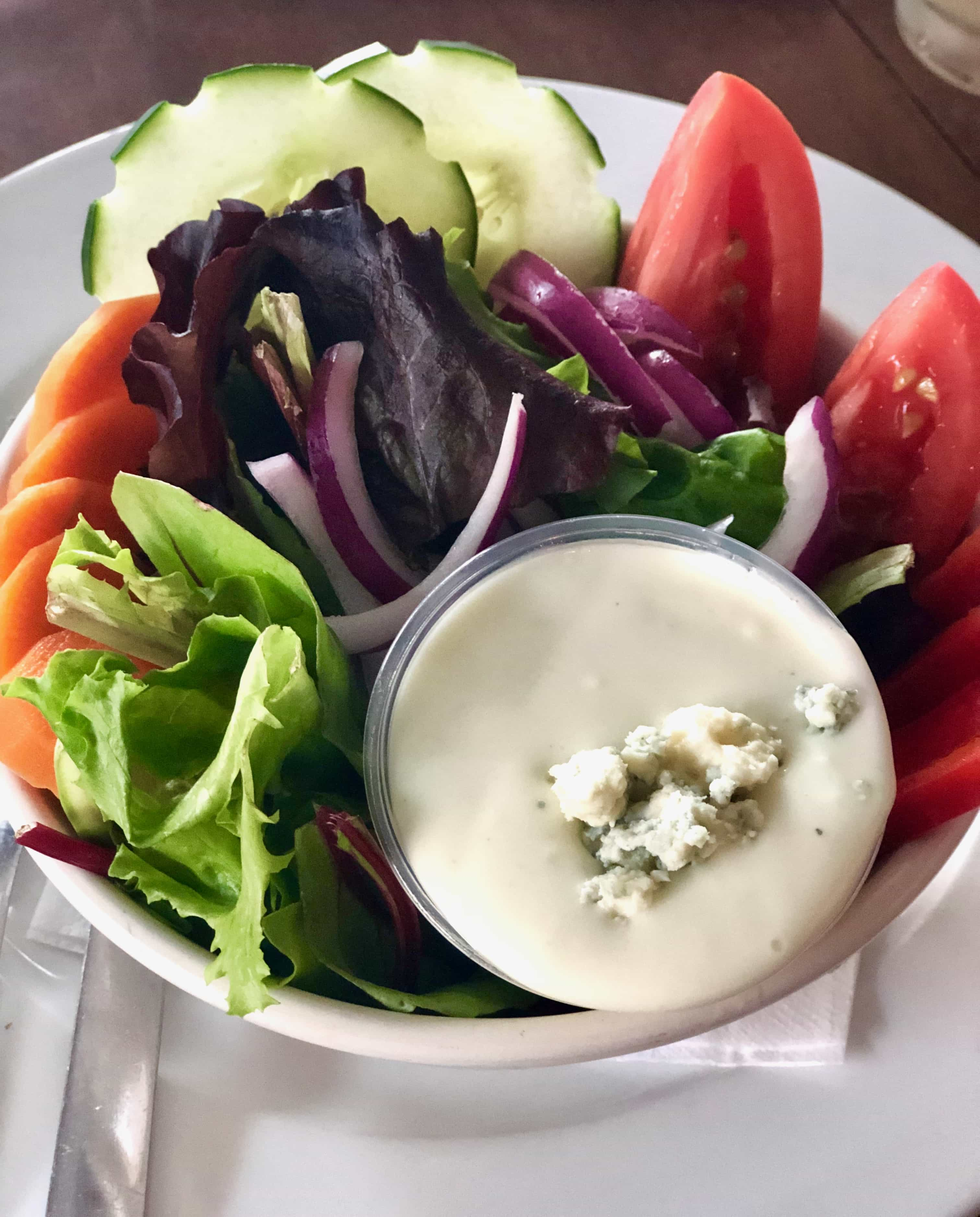 mixed salad with veggies and blue cheese dip in a white bowl