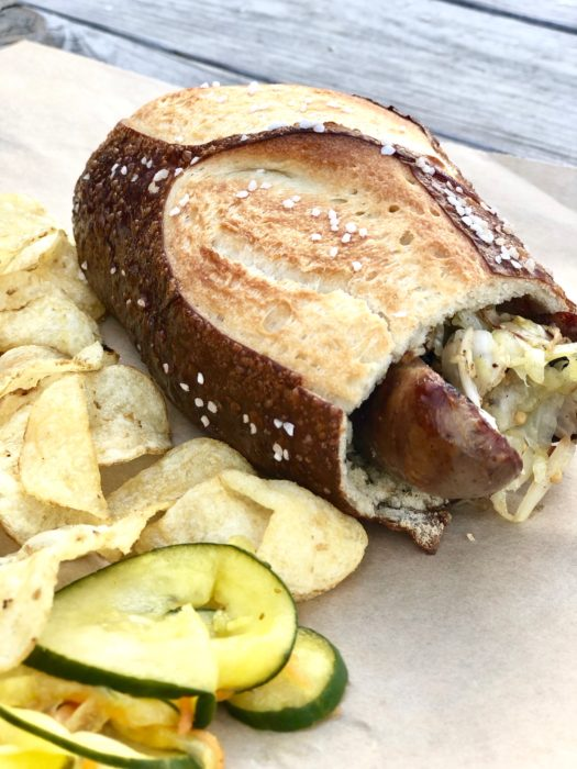 pig missle sausage sandwich in a pretzel bun with chips and a pickle
