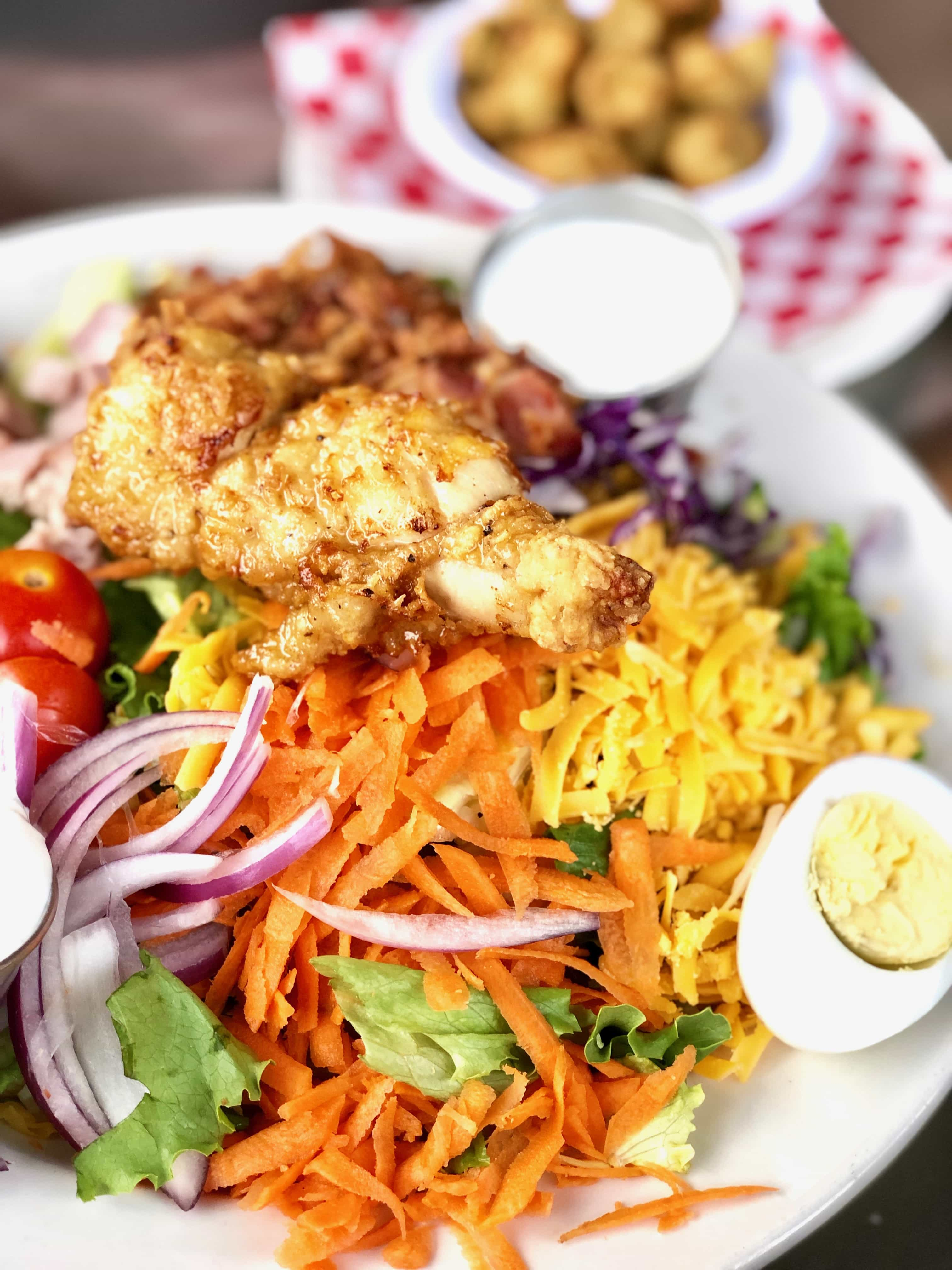 chef salad with boiled eggs, cheese, carrots and tomatoes surrounding a chicken tender