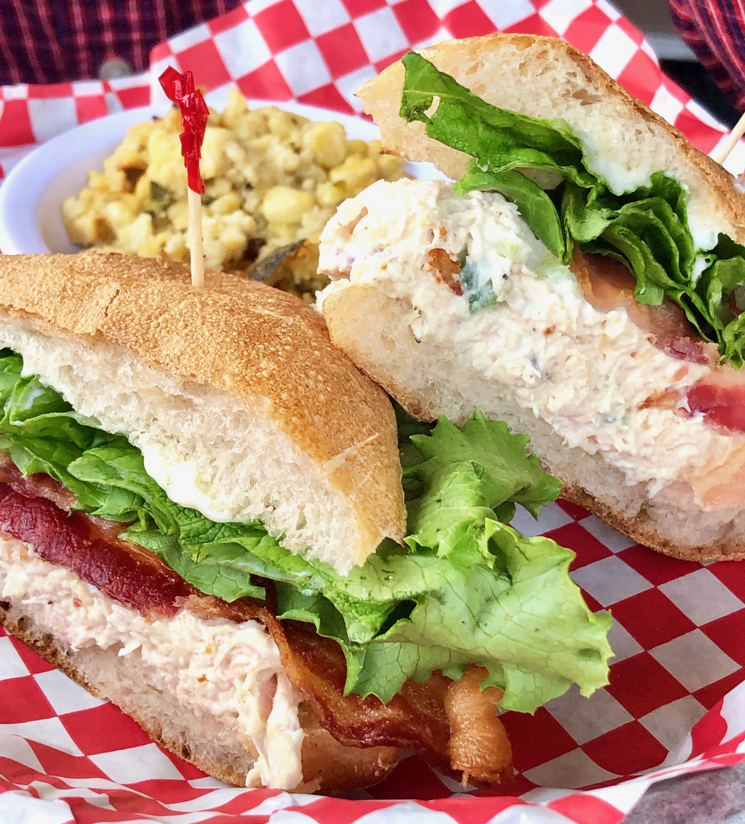 chicken salad sandwich on a ciabatta roll with lettuce and bacon
