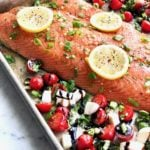 whole salmon on a sheet pan with lemon slices and tomatoes, cheese and basil on the side