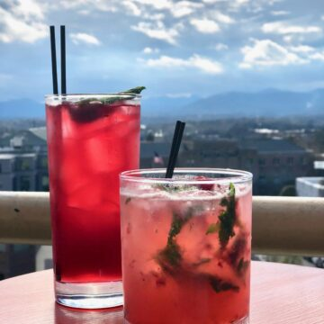 two pink cocktails on a table overlooking the Asheville skyline