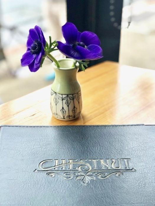 purple flower in vase with menu at Chestnut restaurant