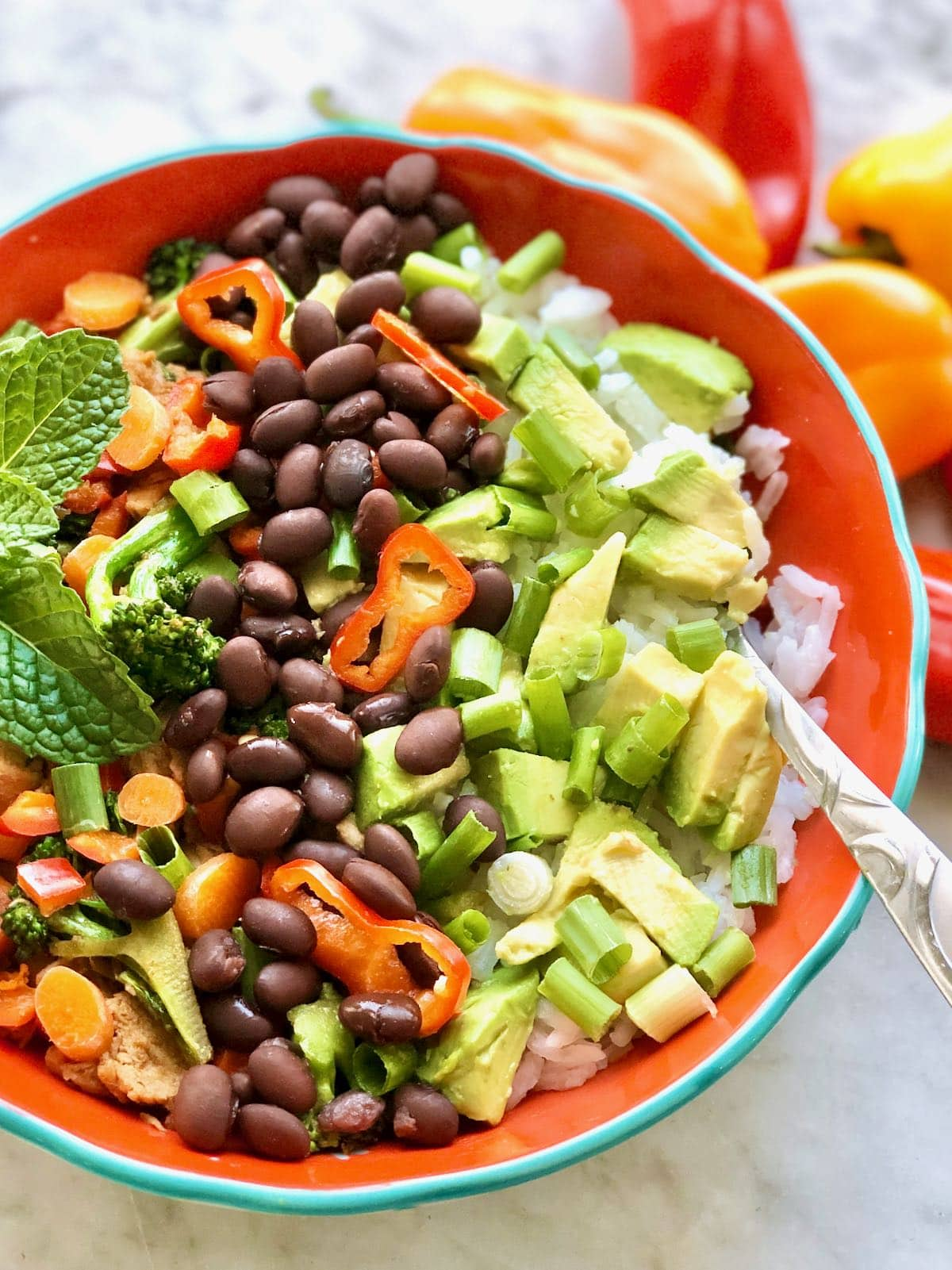 rice bowl topped with avocado, black beans and peppers.