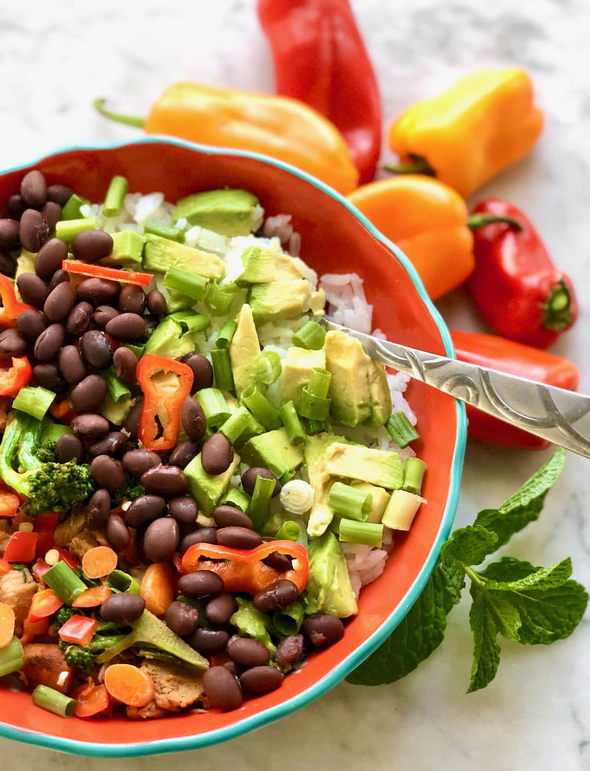 red bowl full of black beans and colorful veggies.