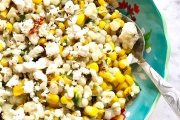 corn in a skillet with feta cheese and onions