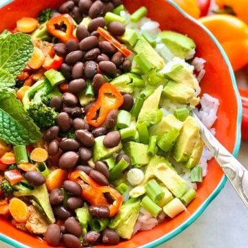 colorful veggies, black beans and avocado served over rice.