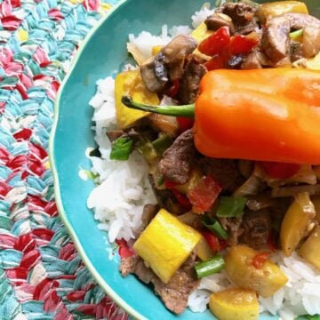 beef and veggies on top of a bed of rice in a blue bowl with a pepper on top