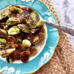 a blue bowl filled with honey mustard brussels sprouts