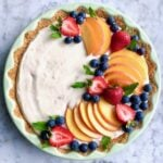 peach tart with berries in green dish