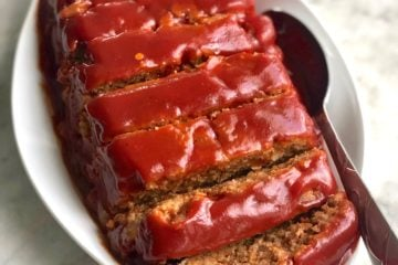 smoked BBQ meatloaf covered with tomato sauce in a white dish