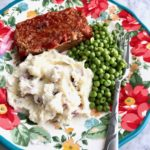 smoked BBQ meatloaf, mashed potatoes and peas on a floral pate