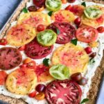 heirloom tart on a sheet pan with a variety of tomatoes in red, green and orange