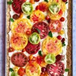 tomatoes in green, red and orange on top of a ricotta tart