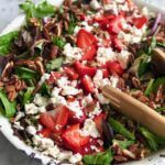 lettuce, strawberries and feta cheese in a white bowl with salad tongs