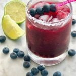 blueberry sriracha margarita in a glass with lime and blueberries