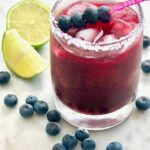 blueberry sriracha margarita in a glass with lime rimmed with salt