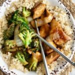 sesame chicken and broccoli in a rice bowl