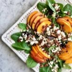 toasted pecan peach salad on a white plate topped with goat cheese crumbles