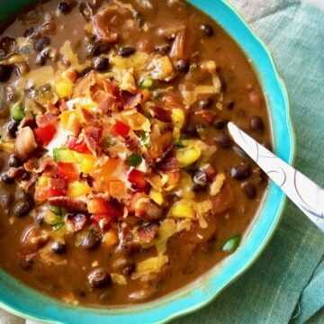 bacon black bean soup in a blue bowl with cheese, bacon, sour cream and peppers on top
