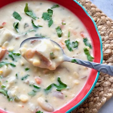 creamy corn chowder in a red bowl with spoon