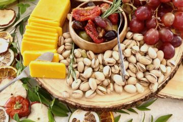 cheese, nuts, fruit and crackers on a wooden board