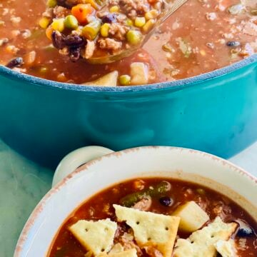 Vegetable Beef Soup in a blue dutch oven with a bowl of it and crackers on top