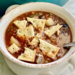 vegetable beef soup with crackers in a white bowl
