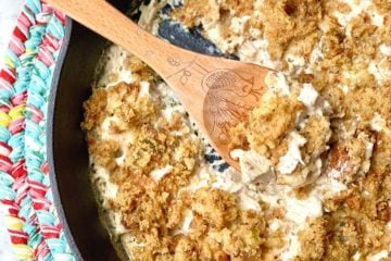 Leftover Turkey Bake casserole with a wooden spoon scooping out of a cast iron skillet