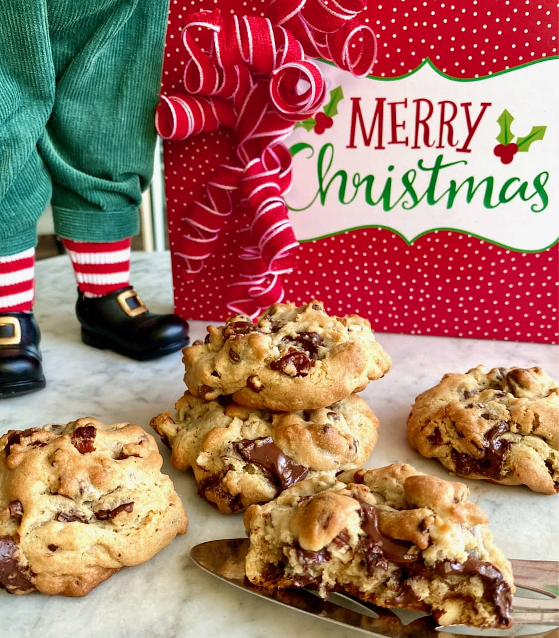 chocolate chip cookies sitting on a white table with a present and Santa standing over them