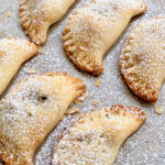 pecan pie turnovers on a cookie sheet with powdered sugar