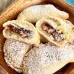 twice baked pecan pie turnovers on wooden serving plates with powdered sugar