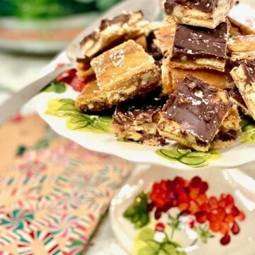 toffee bars with chocolate and dusted with salt on a floral cake plate
