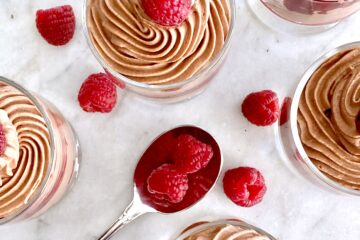 overhead view of chocolate mouse with a spoon and raspberries on a white background