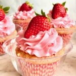 strawberry coconut cupcakes in a glass dish with a strawberry on top