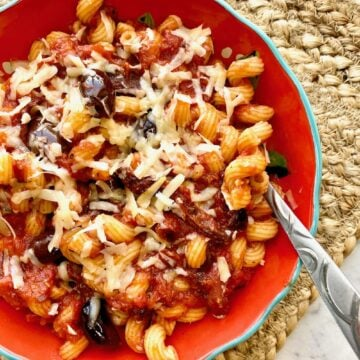 a serving of pasta with sun dried tomatoes, olives and cheese on top in a red bowl