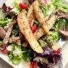 steak and potato salad on a white plate