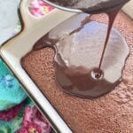 chocolate frosting being poured on top of a hot chocolate cake